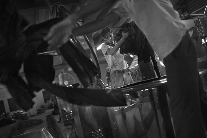 Fashion Victims - Other people´s clothes; Asia, Southasia, India, Gujarat, Ahmedabad, Narol; Workers in a big denim production unit drudge double-shifts to increase their small salary. Often, they are the only ones in a family with a regular income. Fashion Victims - Die Kleider anderer Leute; Asien, Suedasien, Indien, Gujarat, Ahmedabad, Narol; Die Arbeiter einer der großen Denimproduzenten der Stadt arbeiten freiwillige Doppelschichten, um ihren schmalen Lohn aufzubessern. Oft sind sie die einzigen in der Familie mit einem regelmaeßigen Einkommen. Durch den grossen sozialen Druck, sowie die Belastung durch die monotone Arbeit und das fehlende Sonnenlicht, begangen in den letzten Jahren viele Arbeiter Selbstmord.