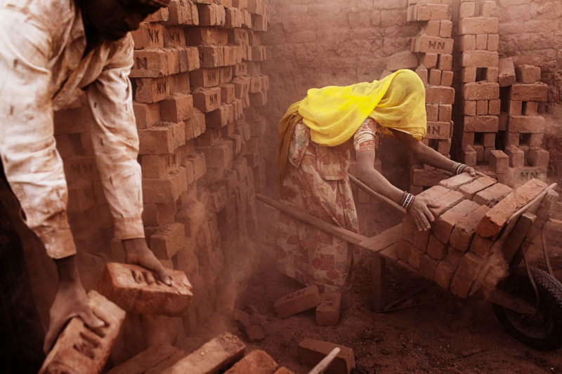 "Asia, South Asia, India, Gujarat, Sarkhej; Workers in a brick factory are taking bricks on a wheelbarrow from the oven. (Extracted from the project ""Majadura – Migrant labourers in India"")"